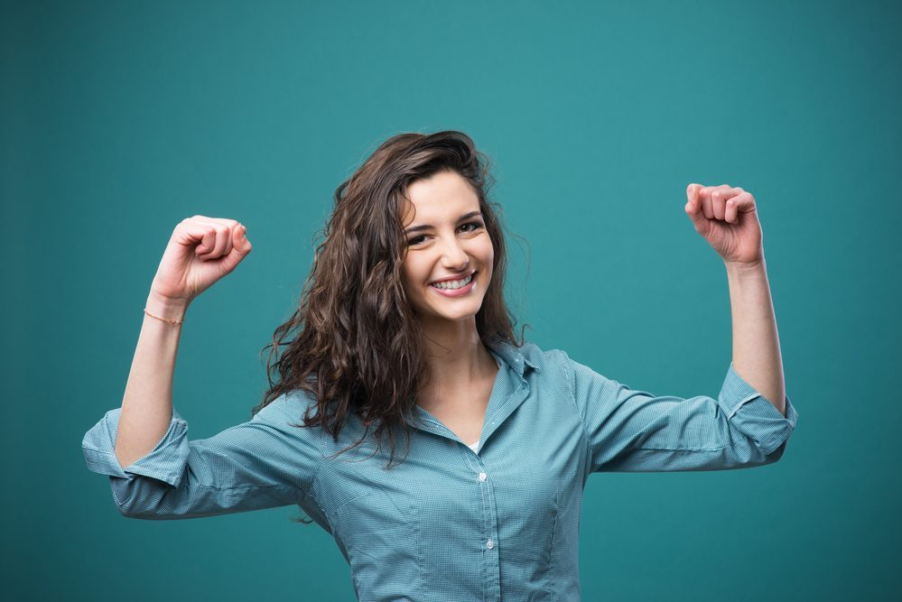 Cheerful young woman smiling with raised fists